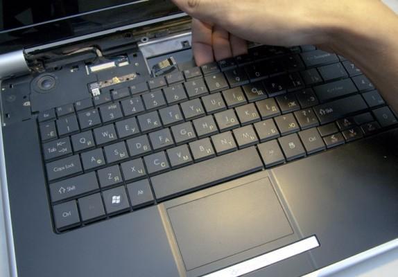 Процесс изъятия клавиатуры из корпуса ноутбука